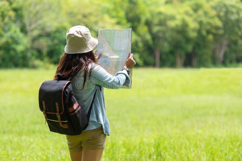 Studenten Aziatische vrouwen en reiziger met de holdingskaart van het rugzakavontuur om richtingen in wildernis bos openlucht voo stock foto's