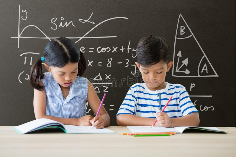 Studenten bei Tisch, die gegen graue Tafel mit Bildung und Schulgraphiken schreiben lizenzfreie stockfotografie