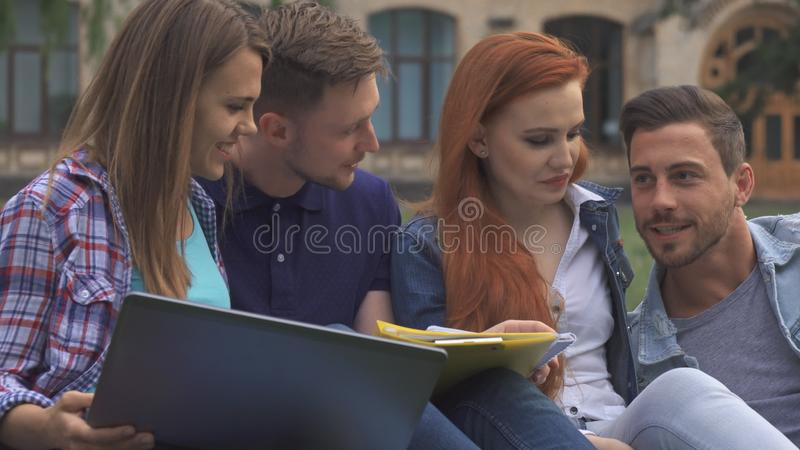 Studenten besprechen etwas auf dem Rasen auf dem Campus lizenzfreies stockfoto