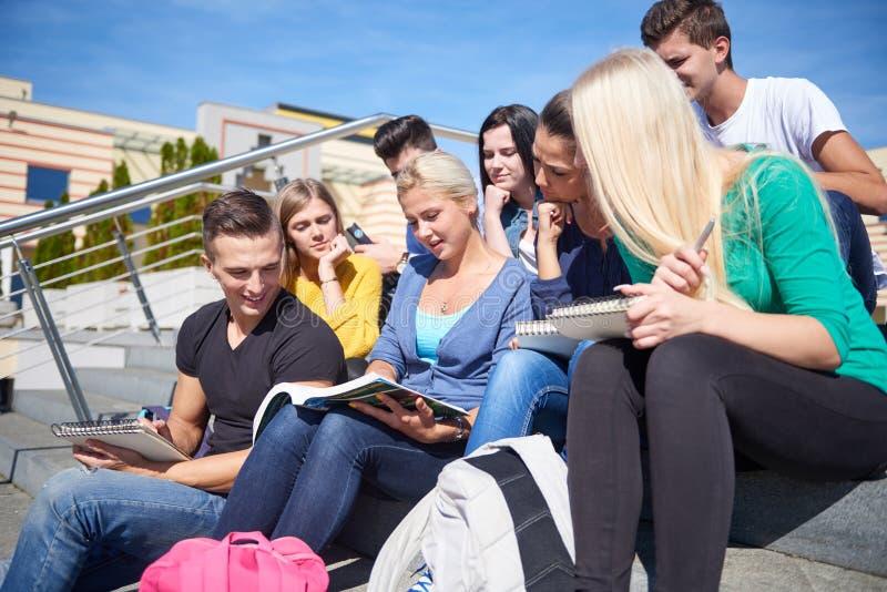 Studenten buiten het zitten op stappen stock afbeeldingen