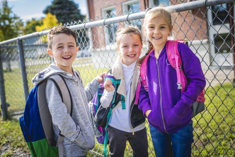 Studenten buiten school die zich verenigen stock foto