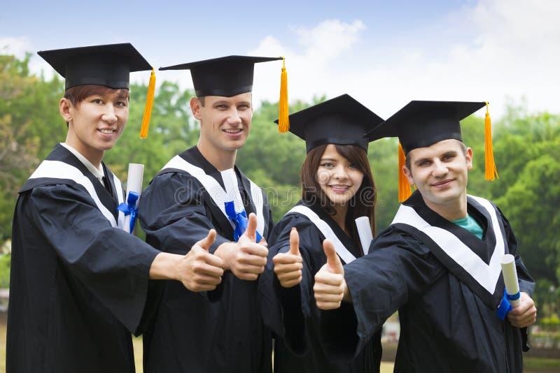 Studenten in der Staffelung bekleidet das Zeigen von Diplomen mit den Daumen stockfotos