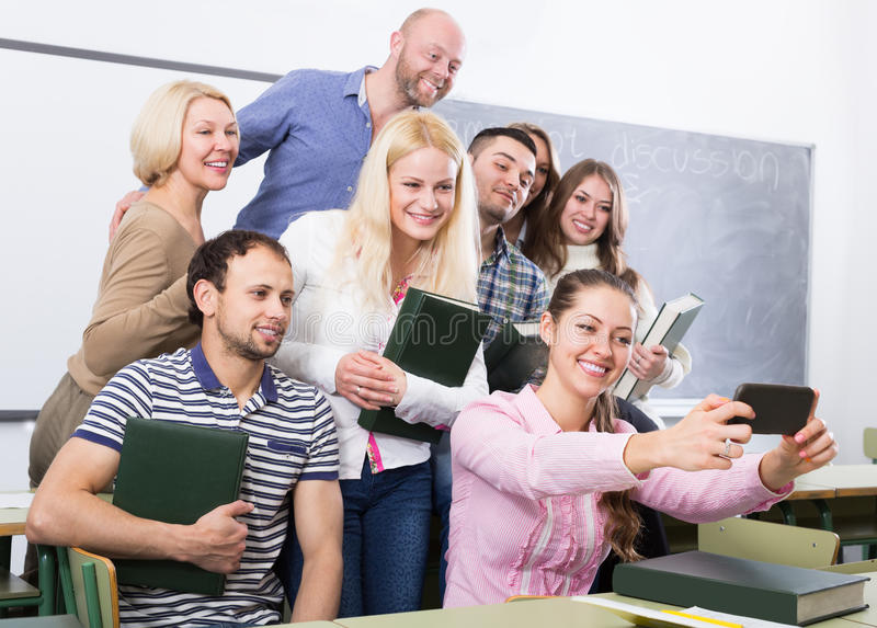 Studenten des unterschiedlichen Alters Gruppe selfie auf Smartphone tuend lizenzfreie stockbilder