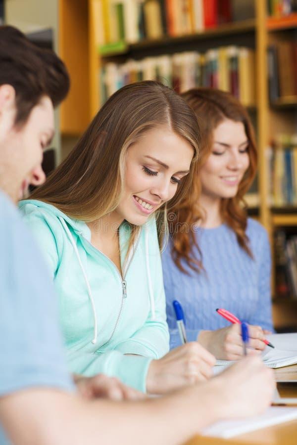 Studenten die aan examen voorbereidingen treffen en in bibliotheek schrijven royalty-vrije stock afbeelding