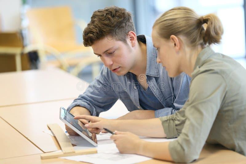 Studenten die aan tablet werken stock afbeelding