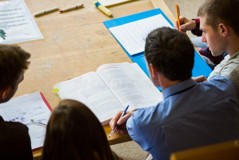 Studenten, die Anmerkungen in die Collegebibliothek schreiben lizenzfreie stockbilder