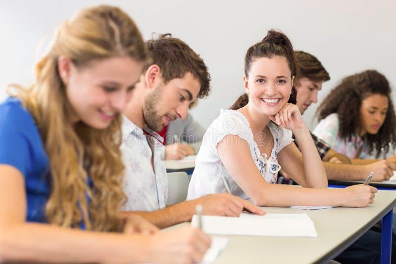 Studenten, die Anmerkungen in Klassenzimmer schreiben stockbilder