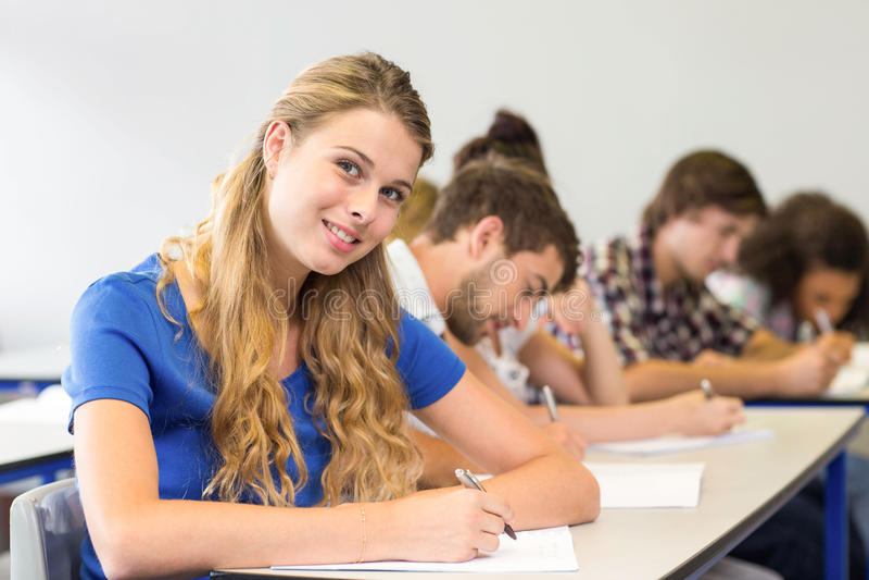 Studenten, die Anmerkungen in Klassenzimmer schreiben lizenzfreie stockfotos