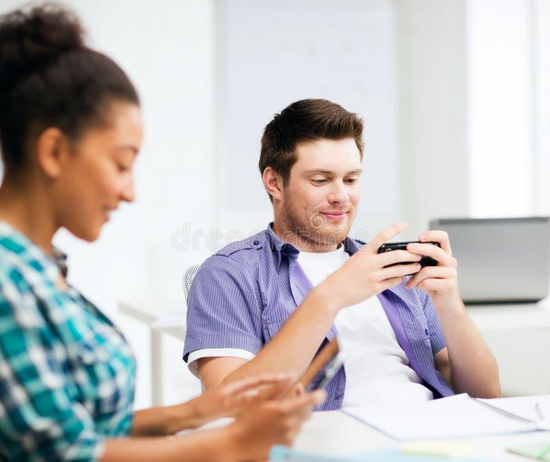 Studenten die apparaten op school bekijken stock fotografie