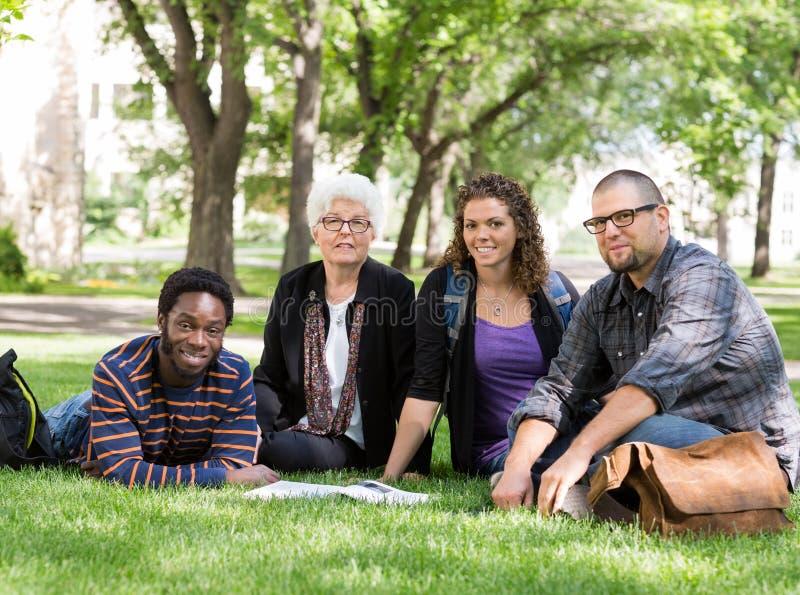 Studenten, die auf Gras am Campus-Park sitzen stockbild