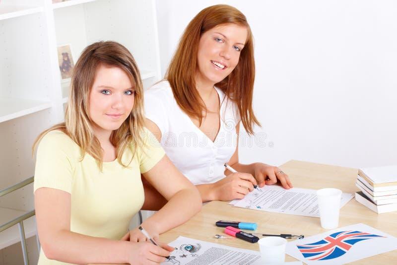 Studenten die bij bureau leren stock foto