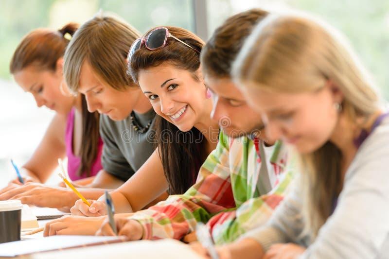 Studenten die bij de tienerjarenstudie van het middelbare schoolexamen schrijven stock fotografie