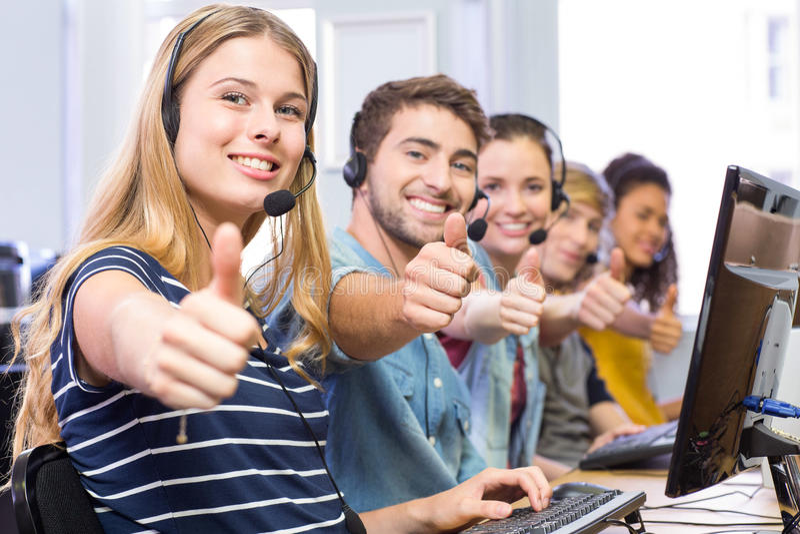 Studenten, die Daumen oben in der Computerklasse gestikulieren lizenzfreies stockbild