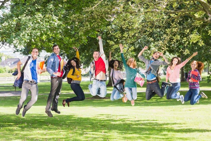 Studenten, die in den Park springen lizenzfreie stockfotos