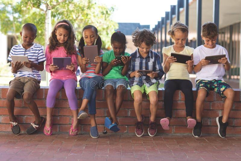 Studenten, die digitale Tablette beim Sitzen auf Backsteinmauer verwenden lizenzfreie stockbilder