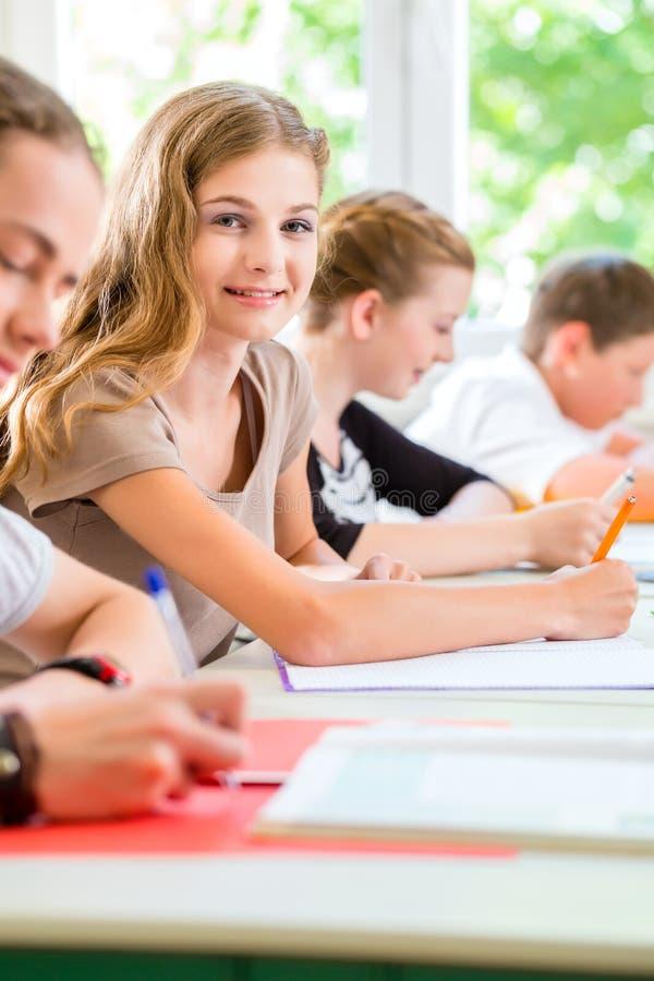 Studenten die een test in zich school het concentreren schrijven stock foto's