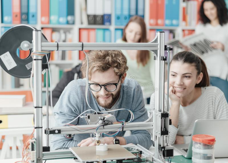 Studenten, die einen Drucker 3D verwenden lizenzfreie stockfotografie