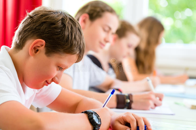 Studenten, die einen Test bei der Schulkonzentration schreiben lizenzfreies stockfoto