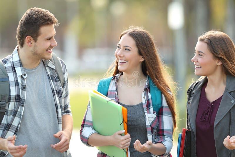 Studenten die en in een campus lopen spreken stock afbeeldingen