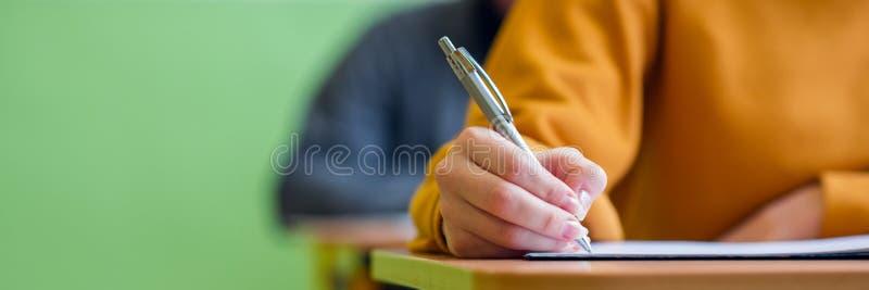 Studenten die examen in klaslokaal nemen Onderwijstest en geletterdheidsconcept Bebouwd schot, handdetail royalty-vrije stock fotografie