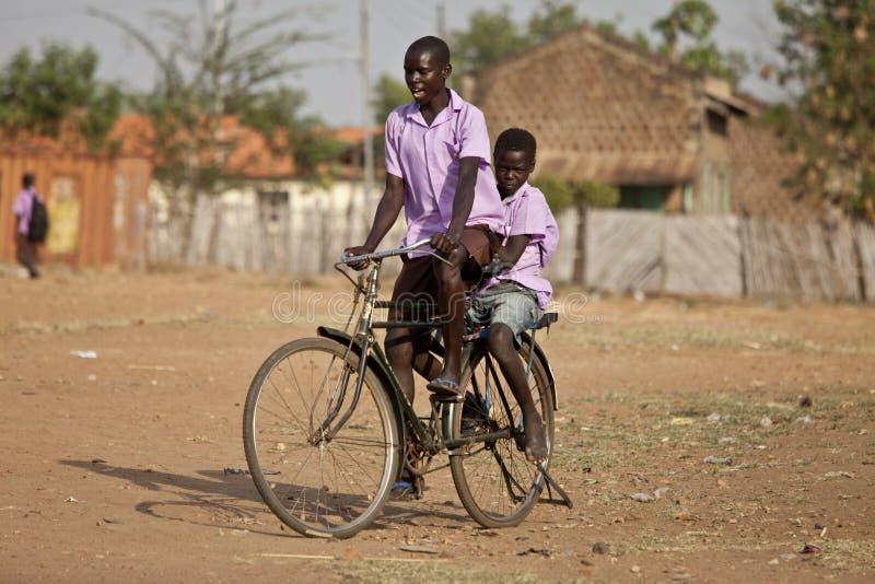 Studenten die fiets in Afrika berijden stock foto