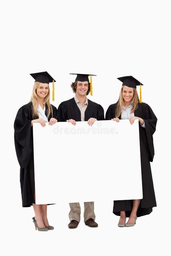 Studenten die in gediplomeerde robe een spatie de houden ondertekenen stock foto's