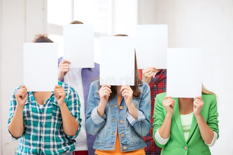 Studenten die gezichten behandelen met lege documenten royalty-vrije stock foto