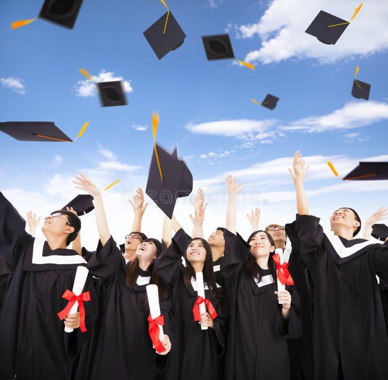studenten die graduatiekappen werpen in de Lucht stock afbeelding