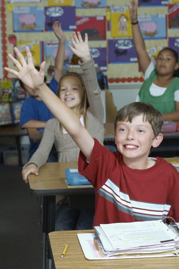 Studenten, die Hände im Klassenzimmer anheben stockfotos