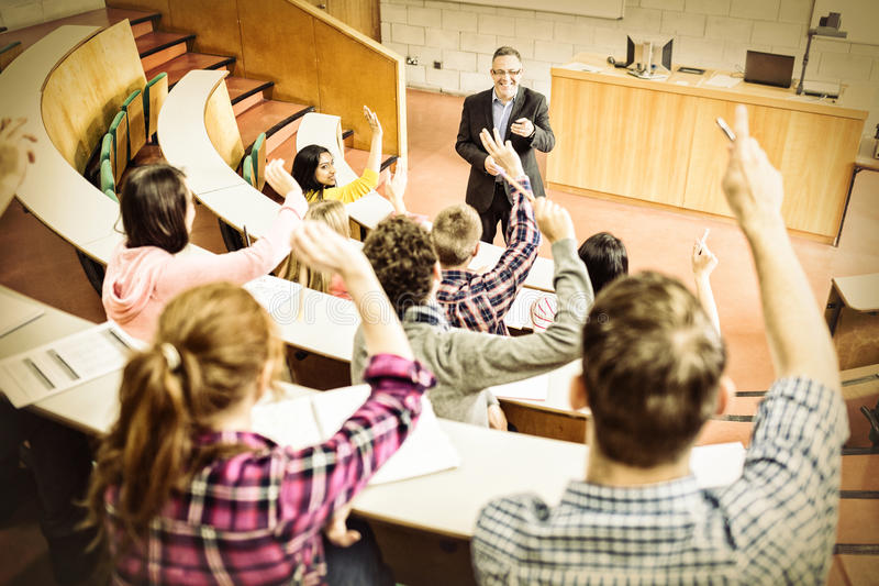 Studenten, die Hände mit Lehrer im Vorlesungssal anheben stockfotos