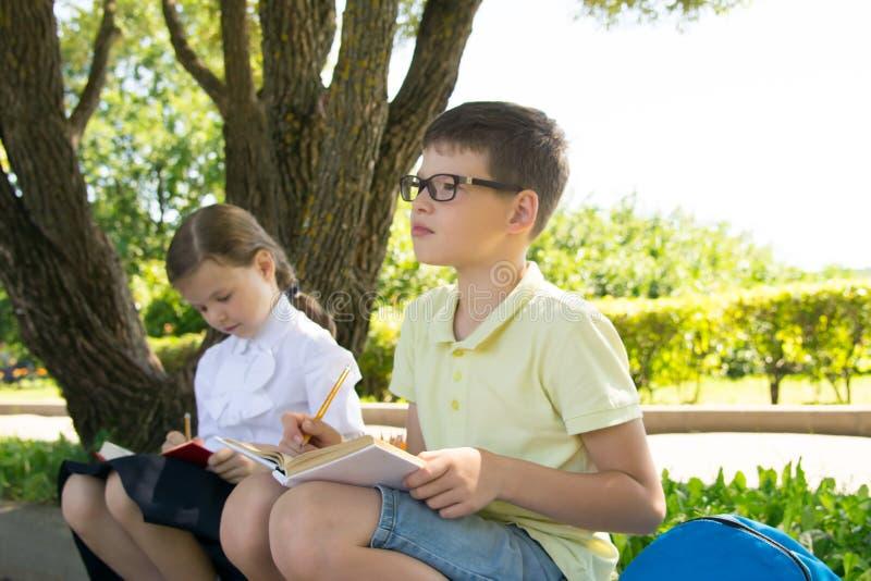 Studenten, die Hausarbeit, im Park in der Frischluft, ein Junge mit Gläsern, Gedanke über die Aufgabe tun stockfoto