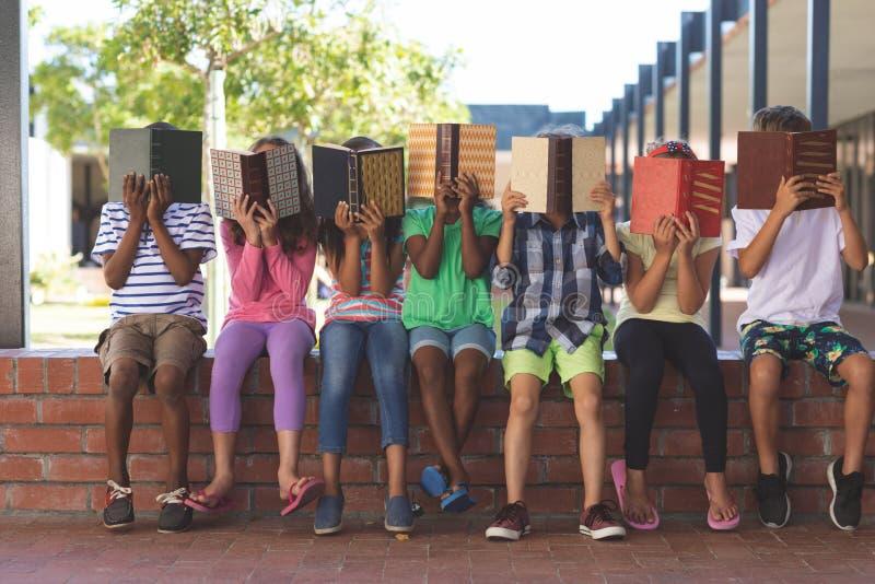Studenten, die hinter Buch beim Sitzen auf Backsteinmauer sich verstecken lizenzfreie stockfotografie