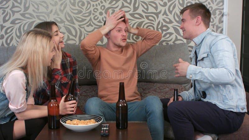 Studenten, die hinter Tabelle, trinkendes Bier sitzen und lustige Geschichte erzählen lizenzfreie stockfotos