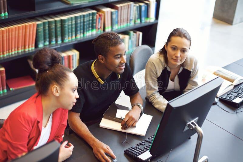 Studenten die informatie over computer voor schoolproject vinden royalty-vrije stock afbeelding