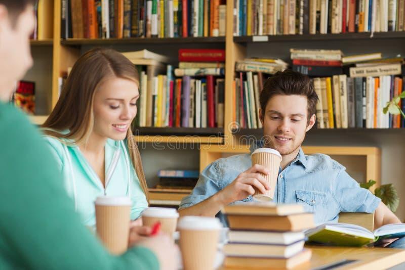 Studenten, die Kaffee in der Bibliothek lesen und trinken lizenzfreie stockfotos