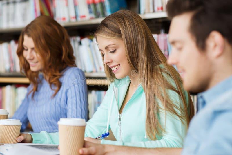 Studenten, die Kaffee in der Bibliothek lesen und trinken lizenzfreie stockbilder