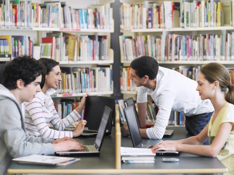 Studenten, die Laptops in der Bibliothek verwenden stockbild