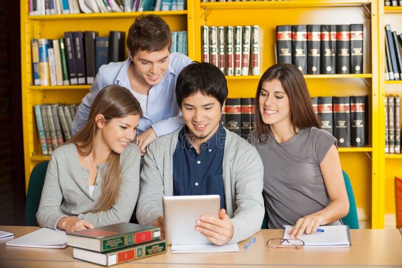 Studenten die met Digitale Tablet samen binnen bestuderen stock foto