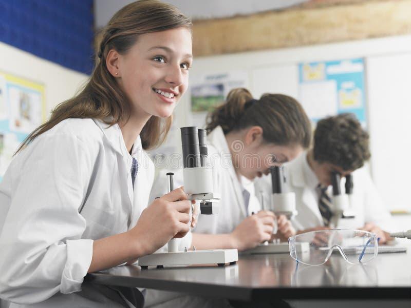 Studenten, die Mikroskope im Labor verwenden stockbild