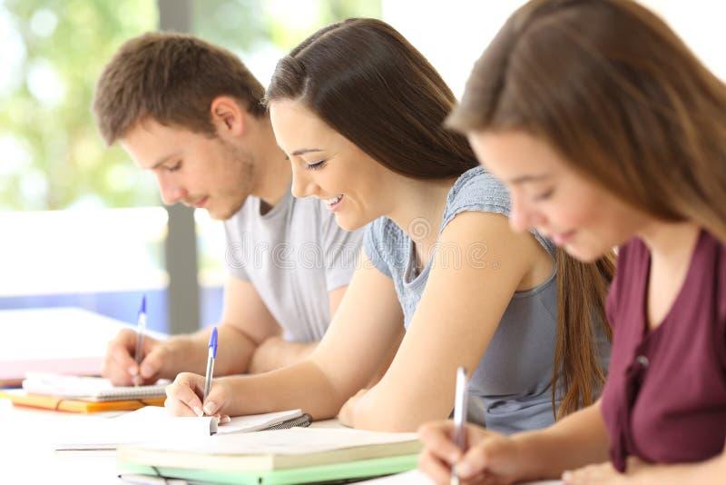 Studenten die nemend nota's in een klaslokaal bestuderen stock foto's