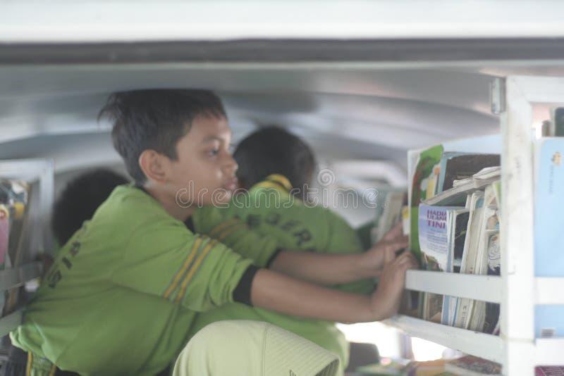 studenten die omhoog een boek in de mobiele bibliotheek een rij vormen te lezen stock foto's