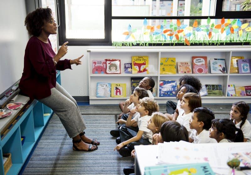 Studenten die op de vloer zitten die aan leraar luisteren stock fotografie