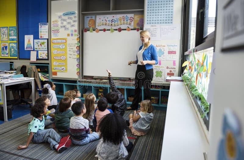 Studenten die op de vloer zitten die aan leraar luisteren royalty-vrije stock afbeelding