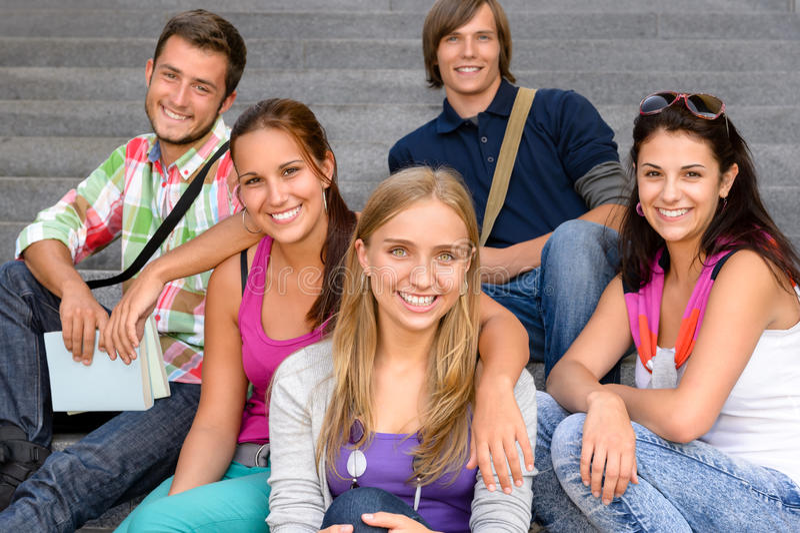 Studenten die op schooltreden zitten die tienerjaren glimlachen stock fotografie