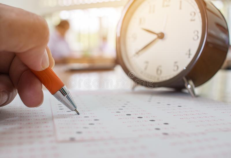 Studenten die optische vorm van gestandaardiseerde examens nemen dichtbij Alarmcl stock afbeeldingen