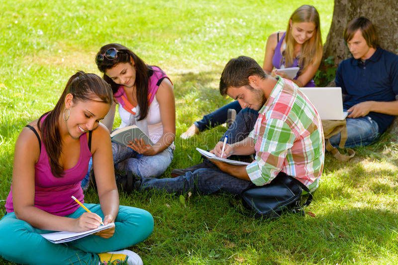 Studenten die in park zitten dat lezing het schrijven bestudeert royalty-vrije stock foto