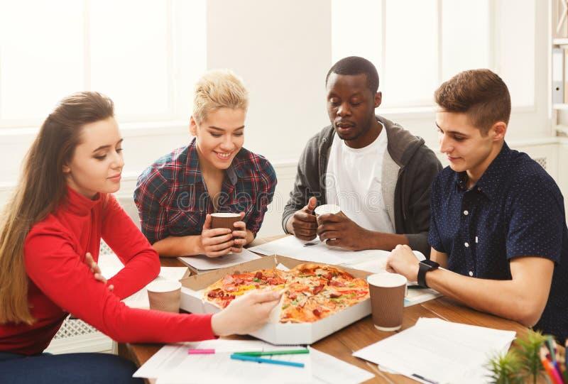 Studenten, die Pizza lernen und essen stockbild