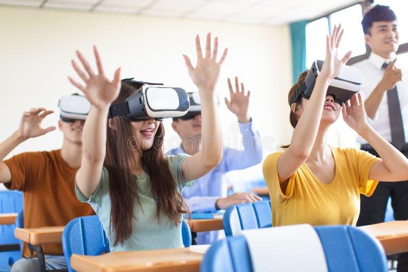 Studenten die pret met nieuwe technologie vr hoofdtelefoon hebben in klaslokaal stock afbeeldingen