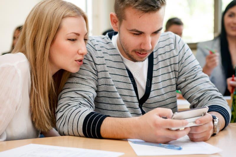Studenten die telefoon met behulp van tijdens klasse royalty-vrije stock fotografie
