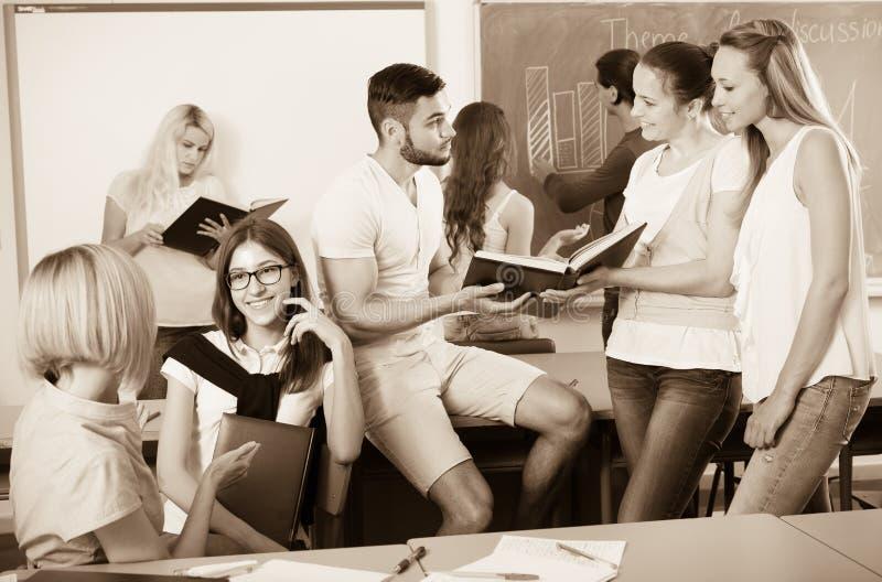 Studenten die terwijl het zitten in de ruimte babbelen stock foto